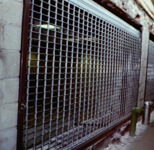Straight link pattern grille motorized coiling security gate. Steel and aluminum reverse mounted. (Brooklyn NY)