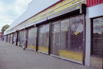 Entire Strip mall of new grille type see through chain operated roll down gate in Brick Pattern (Queens NY) After Photo