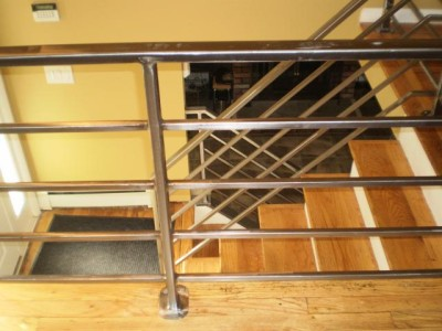 Welded tube steel and square bar polished interior railings plate mounted to wood floor. (Yonkers, NY)