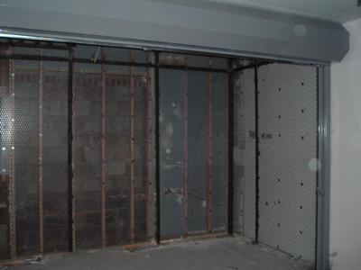 Frame less expanded metal mesh bolted to structural steel support tubes with solid roll down gate for storage room with roof. Different gauges and spacing available. (Brooklyn, NY)