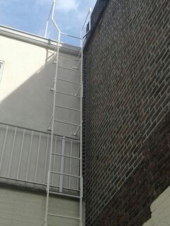 Simple steel fixed roof access ladder braced to building and widened at top. Fabricated in sections and thru bolted together upon installation for ease of positioning and loading to site. (Manhattan, NY)