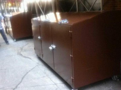 Custom steel garbage pale bins with lockable slidebolts top and front on 5 inch wheels,painted brown.