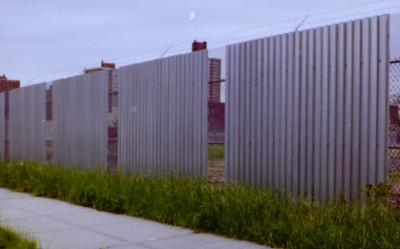 Expanded metal and corrugated steel deck combo 10′ fence with barded wire. (Queens, NY)