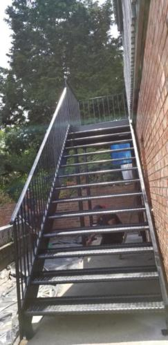 open tread diamond plate steel stairs with support columns and half inch picket railings, all fully welded.